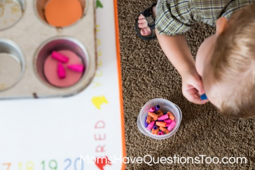 Sorting erasers by color from floor to table for gross motor development - Moms Have Questions Too