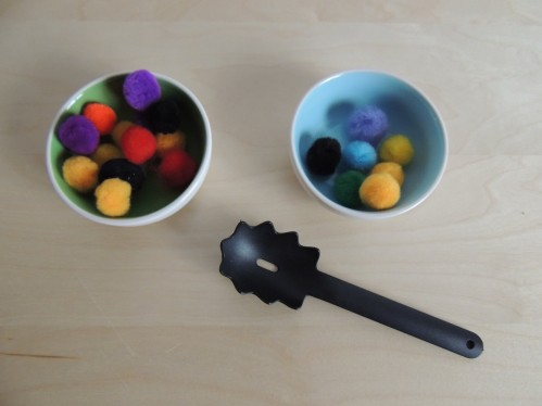 Spoon pompoms from one bowl to another using a kid sized spaghetti spoon