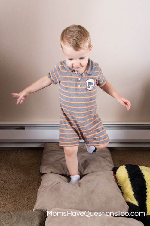 Help your toddler improve their gross motor skills by walking on pillows - Moms Have Questions Too